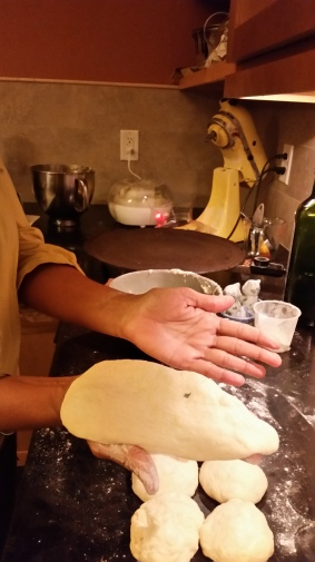 Flatten dough ball by transferring it from one palm to another